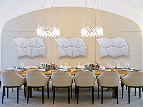 Vista di un tavolo diplomatico con alle spalle pannelli fonoassorbenti di design
